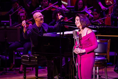 A man smiling in the background while he plays the piano and a woman in a pink dress smiles behind a microphone