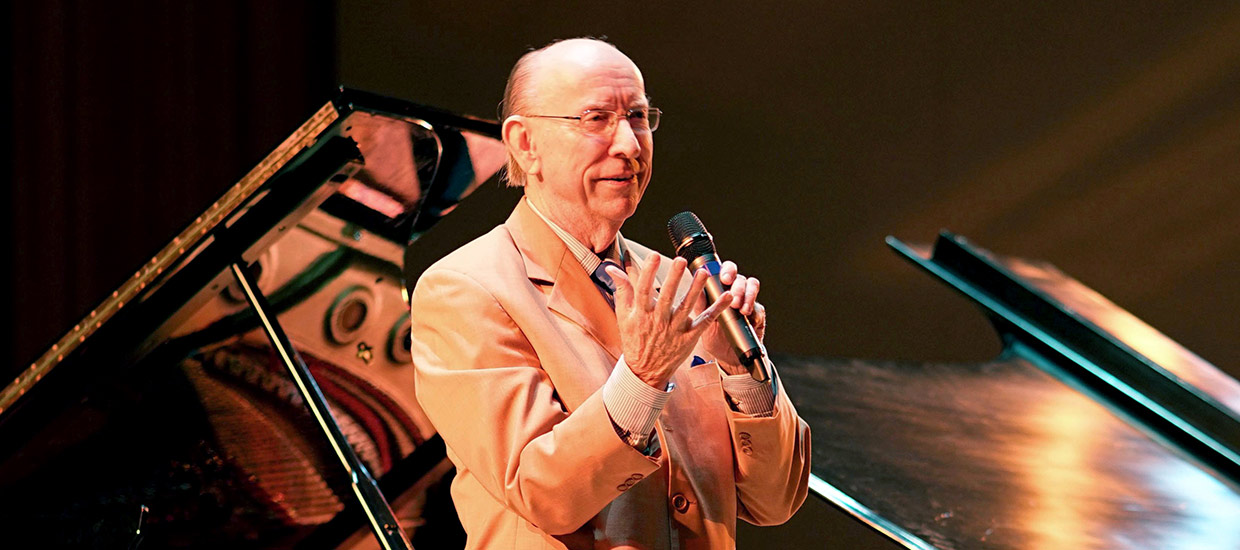 An older gentleman in a tan suit is speaking on stage with a microphone in his hand with a piano in the background.