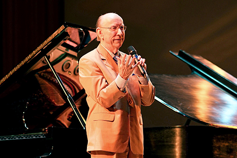 A man in a tan suit speaks into a microphone as he stands in front of 2 pianos