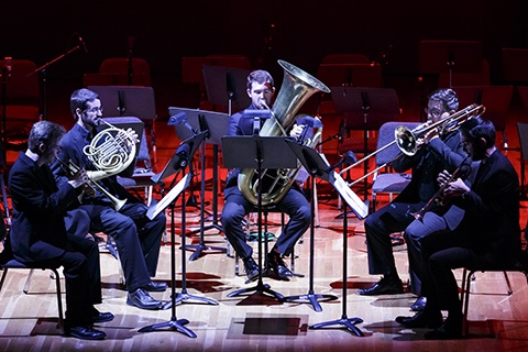 A group of brass players in suits perform on stage