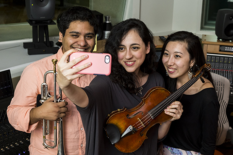 Musicians pose with their instruments for a selfie in a recording studio on campus